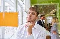 Business Mann schaut nachdenklich auf Haftnotizen