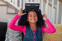 Happy african american girl sitting on sofa, using vr headset and having fun