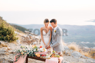 The bride and groom are cutting a cake during a buffet table after the wedding ceremony on Mount Lovcen and smiling