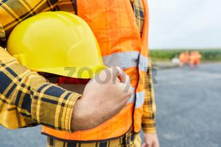 Arbeiter auf Baustelle im Straßenbau mit Schutzhelm