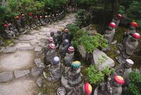 Stairs surrounded by Buddha statues with knitted hats at the temple Diasho-in in Miyajima, Japan