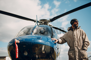 Portrait of helicopter pilot standing near vehicle in field airport