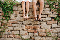 Legs of a man and a woman sitting side by side on the stone fence