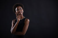 Young black woman trying to find best solution. African american female having doubtful expression looking side away and holding her chin with hand on black background.