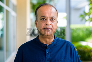 Portrait of Indian man face outdoors looking at camera