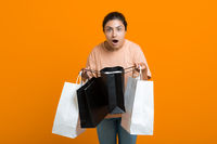 Indian woman holds shopping bags in hands. Sale and Black Friday concept.