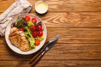 Healthy salad with grilled chicken breast copy space