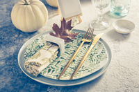 Place setting for Thanksgiving in vintage style with pumpkins and autumn leaf