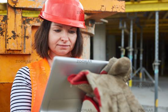 Frau mit rotem Schutzhelm und Tablet Computer