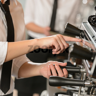 Waitress operating espresso machine coffee house