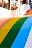 Rainbow multicoloured slide in aqua park in kids playground. Summer time activity outdoors with family. Lgbtq colours of pride