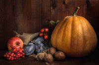 pumpkin and other fruits on a dark wooden background in a rustic style
