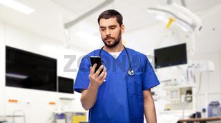 doctor or male nurse using smartphone