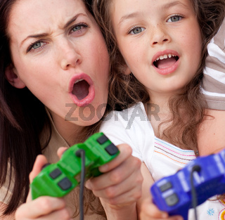 Excited mother and her daughter playing video games