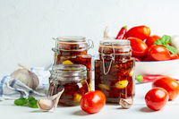 Homemade dried tomatoes with garlic and olive oil in glass jars.
