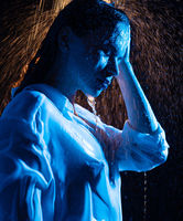 Woman in wet shirt having shower in the dark