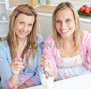 Cheerful friends eating an ice cream and smiling at the camera in the kitchen
