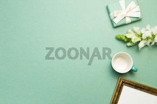 Gift box, white flower, cup, picture frame on green background. flat lay, top view, copy space