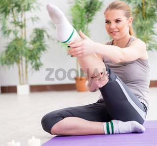 Young woman exercising in sports hall in healthy concept