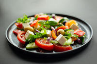 Greek salad on black plate