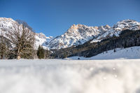 Sunny winter landscape in the nature: Mountain range, snowy trees, sunshine and blue sky