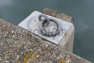 Heavy duty metal ring embedded on dockside with harbour water in background