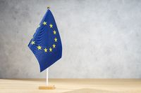 European Union table flag on white textured wall. Copy space for text, designs or drawings