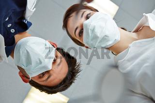 Zahnarzt und Zahnarzthelferin schauen von oben