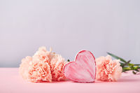 Bouquet of pink carnations and decorative heart. Design concept of holiday greeting with carnation bouquet on pink background