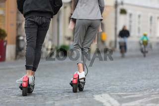 Rear view of unrecognizable trendy fashinable teenagers riding public rental electric scooters in urban city environment. New eco-friendly modern public city transport in Ljubljana, Slovenia.