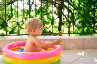 Wet child sitting in a small inflatable pool and catching soap bubbles