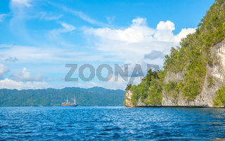 Coastal Rock With Rainforests and Yacht in the Distance