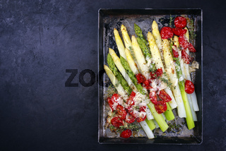 Traditional backed white and green asparagus with tomatoes and parmesan served as top view on a rustic metal tray