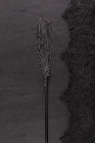 Black whip on leather background with lace from above.