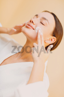 Young woman applying cosmetic white cream on her face