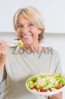 Smiling mature woman eating salad