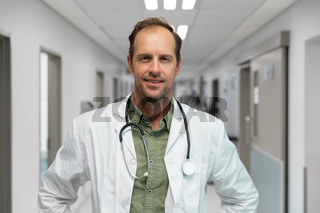 Portrait of smiling caucasian male doctor standing in hospital corridor