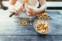 Farm holidays: Woman is preparing delicious chanterelle mushrooms on an old rustic wooden table