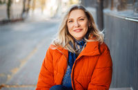 Happy smiling middle aged woman in orange down jacket sitting on concrete stairs outdoors