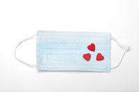 chirurgische Maske und rote Herzen auf weiß