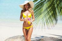Girl in bikini with cocktail on beach
