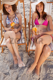 Young women laughing in deck chairs while holding fruit cocktails