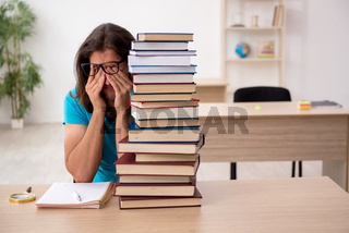 Young male student and a lot of books in the class