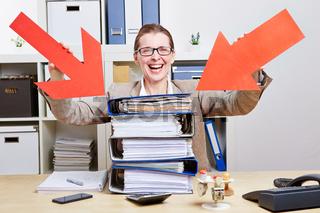 Frau im Büro zeigt mit Pfeilen auf Stapel Akten