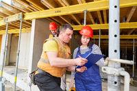Handwerker und Architektin mit Checkliste auf Baustelle