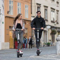 Trendy fashinable teenagers riding public rental electric scooters in urban city environment. New eco-friendly modern public city transport in Ljubljana, Slovenia