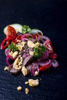 thailändischer Fleischsalat auf schwarzem Schiefer