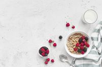 Breakfast bowl with granola, muesli, raspberry, blackberry on gray table