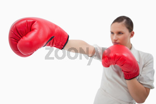 Businesswoman punching something with boxing gloves