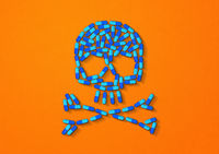 Skull made of blue capsule pills. Orange background